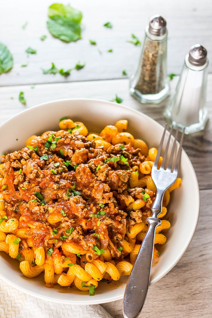 A plate of curly pasta topped high with Greek Style Meat Sauce {Makaronia Me Kima}