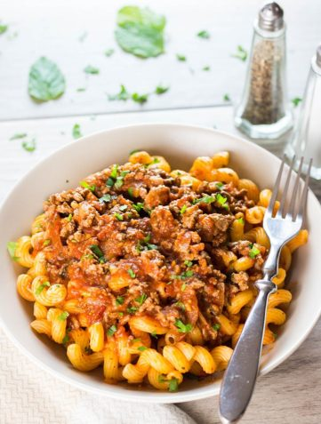 A plate of curly pasta topped high with Greek Style Meat Sauce