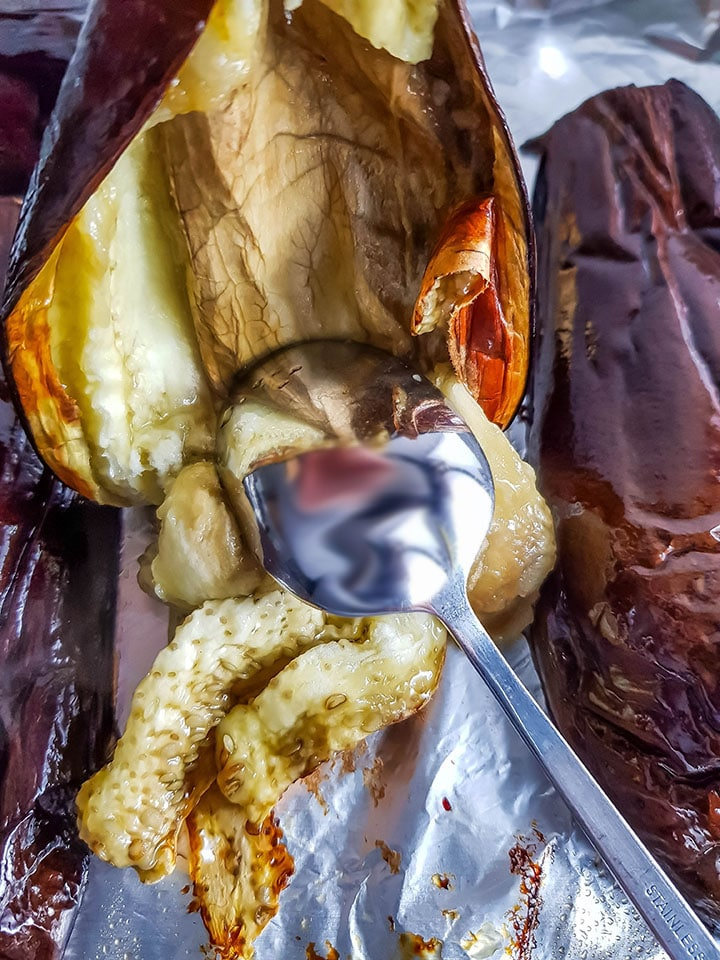 The flesh of the eggplant being scraped out of the skin with a spoon