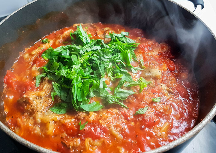 The chopped basil added to the pan with the tomato sauce