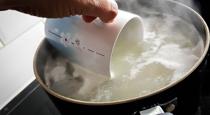 a mug scooping out some cooking water from the pot of pasta