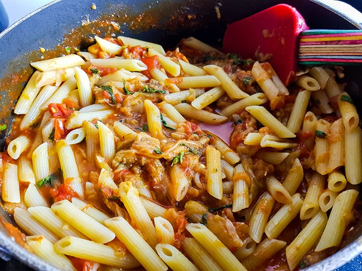 The pasta added to the sauce in the pan