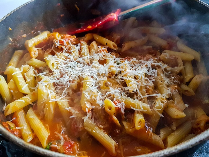 The freshly grated cheese added to the pasta and sauce in the pan