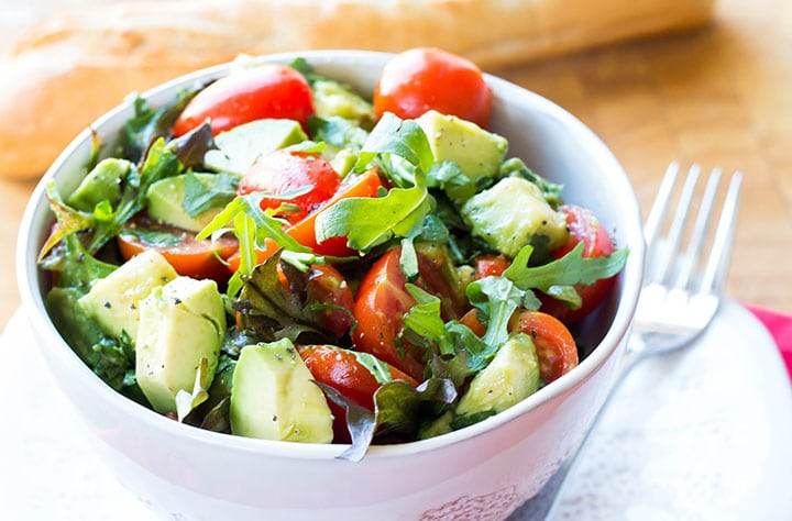 A bowl of bright and colorful tomato avocado salad with some bread in the background.