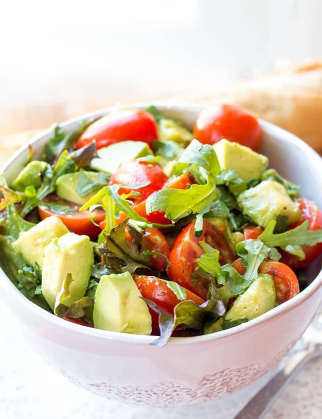 a bowl of the vibrant and colorful tomato avocado salad with some bread in the background