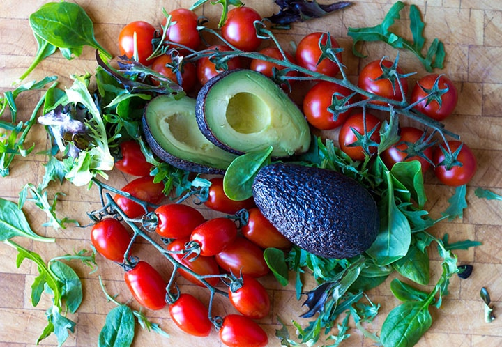 a cutting board covered in cherry tomatoes, still on the vine, avocado and fresh greens