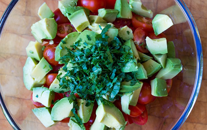 The herbs added to the salad bowl with the avocado and tomatoes