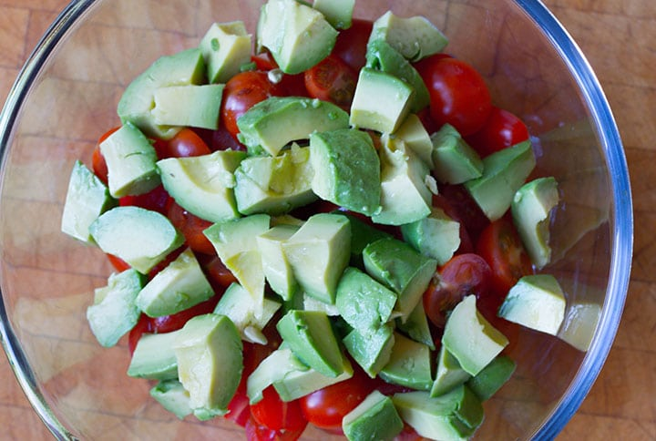 The avocado added to the salad bowl with the tomatoes