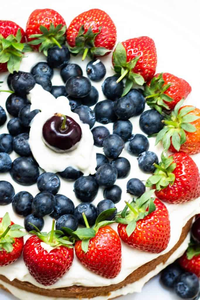 fruit on top of a cake with whipped cream