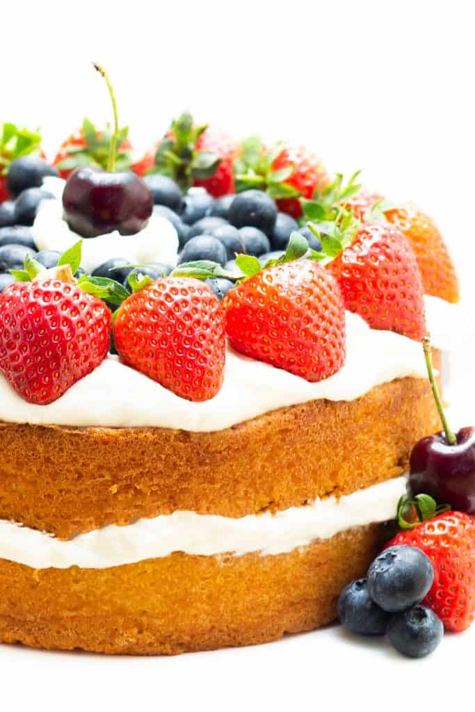 A layer cake topped with cream and fruit