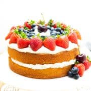 A layer cake on a cake stand topped with cream and fruit