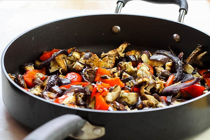 The roasted vegetables added to the pan
