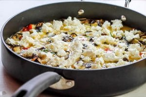 The feta crumbled over the egg and vegetable mixture