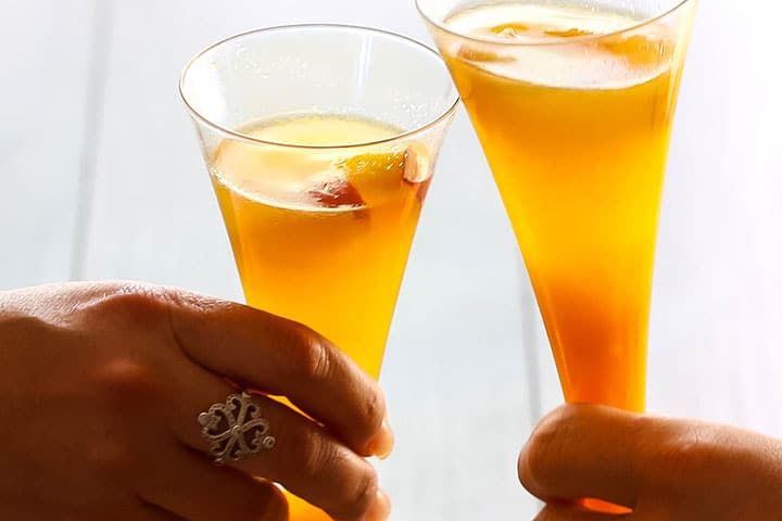 two glasses of Bellini Cocktail clinking together