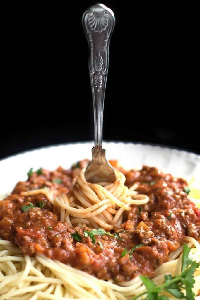 A fork twirling the Spaghetti Bolognese on a plate