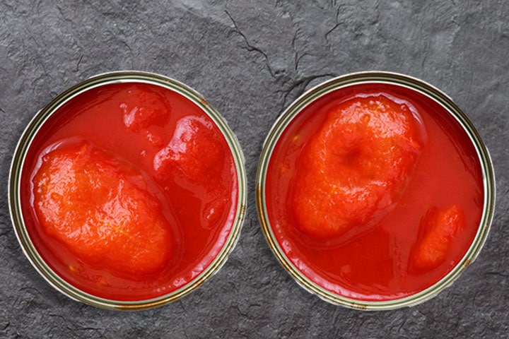 two open cans of whole tomatoes from above