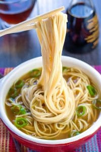 A bowl of quick and easy Chinese noodle soup with chopsticks holding some noodles above the bowl