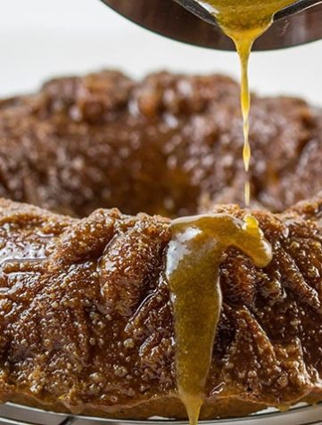 Caramel Apple Bundt Cake with the caramel sauce being poured over it
