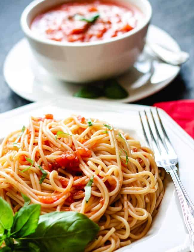 A plate of spaghetti with tomato sauce with a fork next to it and fresh basil near the dish