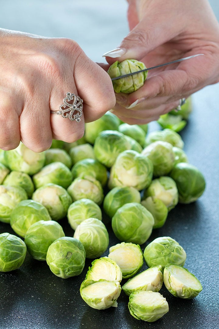 A cross being cut through the stem of a Brussels sprout