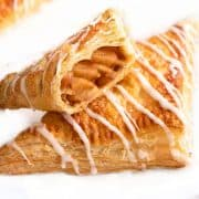 two apple turnovers on a plate with o