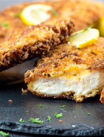 Crispy Breaded Chicken Cutlets on a dish with a piece cut off showing the juicy meat