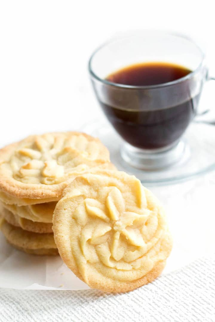 One beautiful Vanilla Shortbread Cookie sitting up against a stack of more cookies with coffee on the background.