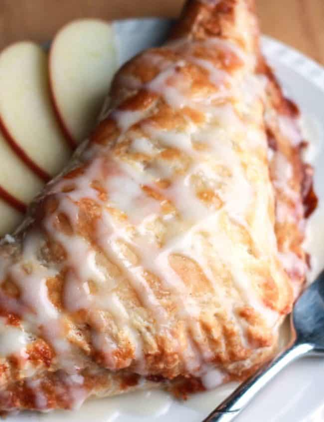 A crispy. golden brown apple turnover on a plate drizzled with icing. A fork and some sliced apples are beside it on the plate