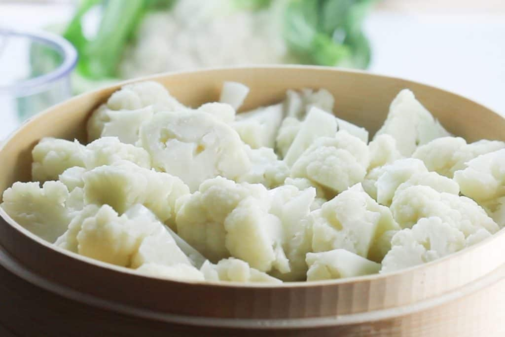 a steamer filled with freshly steamed cauliflower