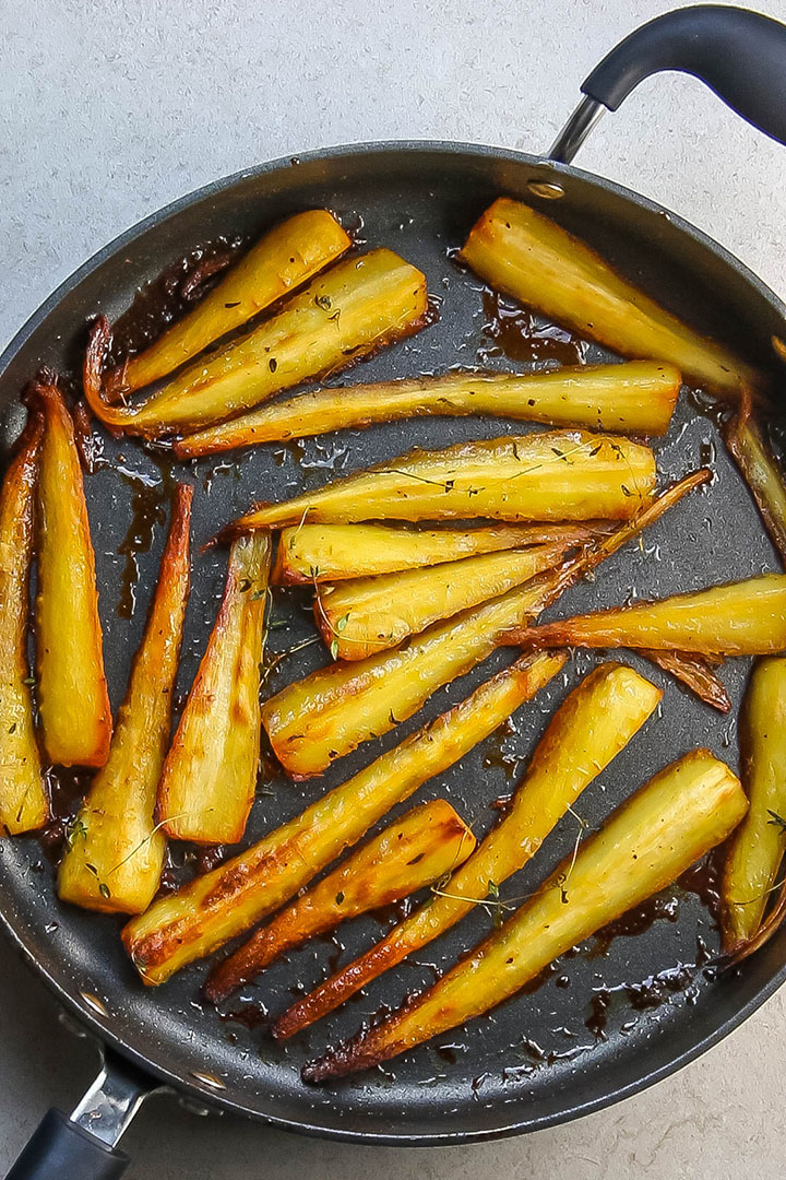 Honey & Maple Roasted Parsnips golden and brown in a pan fresh from the oven