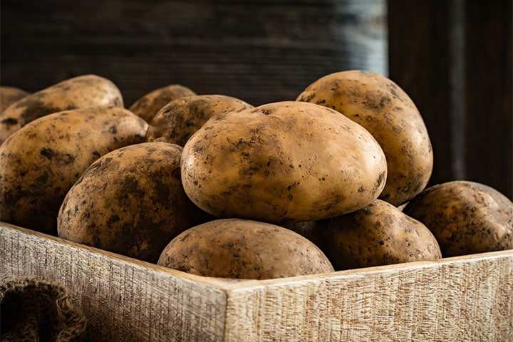 a box full of raw potatoes