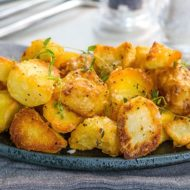A dish piled high with golden, Crispy Roast Potatoes