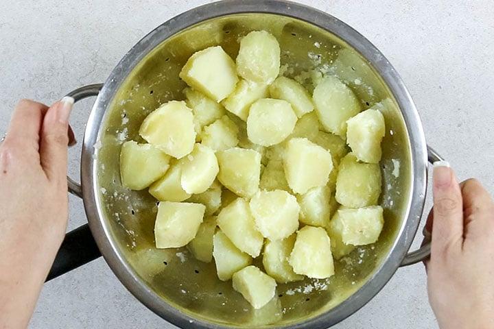 Potatoes in a strainer being shaken