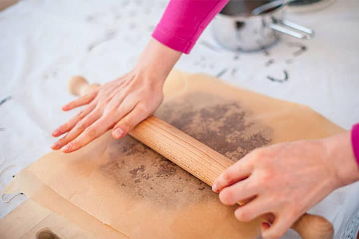 Cookie dough being rolled between two sheets of baking paper
