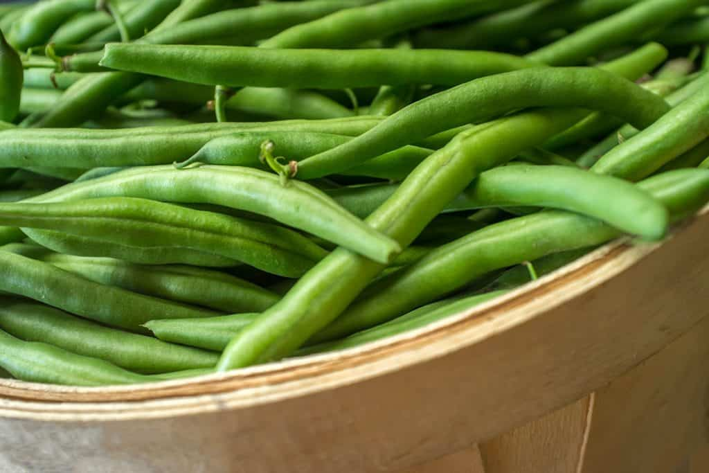 a close up of a basket of green beans
