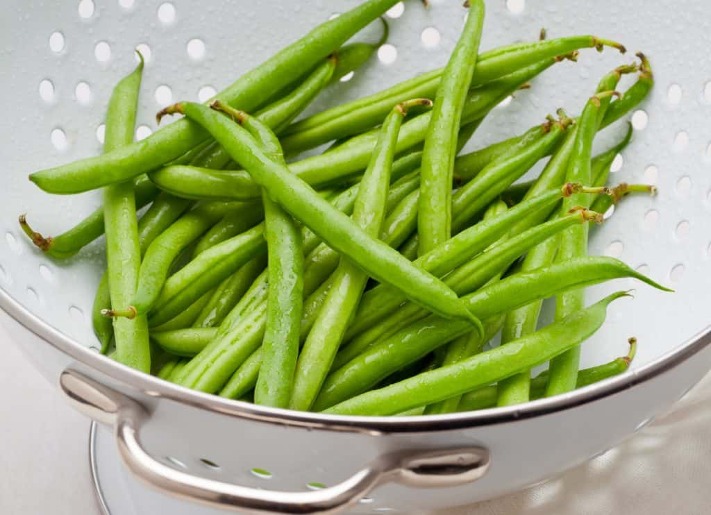 a close up of green beans in a colander