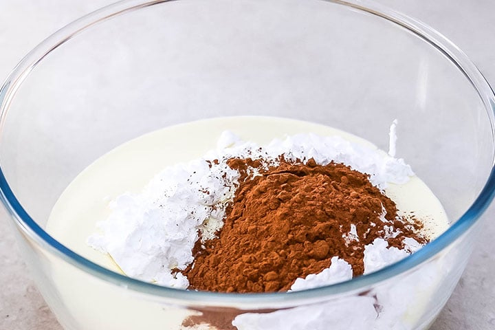 The cocoa powder added to the cream mixture in the bowl