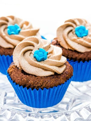 Three chocolate cupcakes with Chocolate Whipped Cream Frosting and decorated with little blue roses