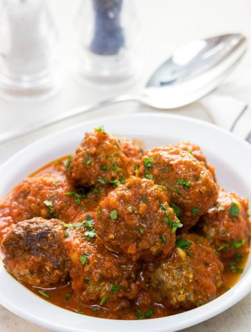 A dish full of Low Carb Italian Meatballs sprinkled with fresh parsley.