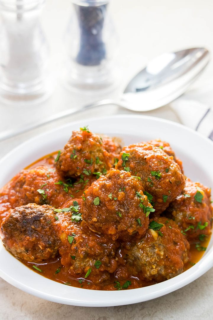 A dish of Meatballs in red sauce sprinkled with fresh parsley.
