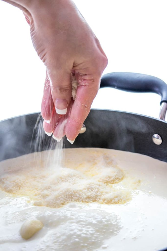 The cheese being added to the sauce in the pan