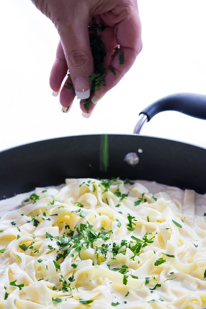 the parsley being added to the Fettuccine Alfredo