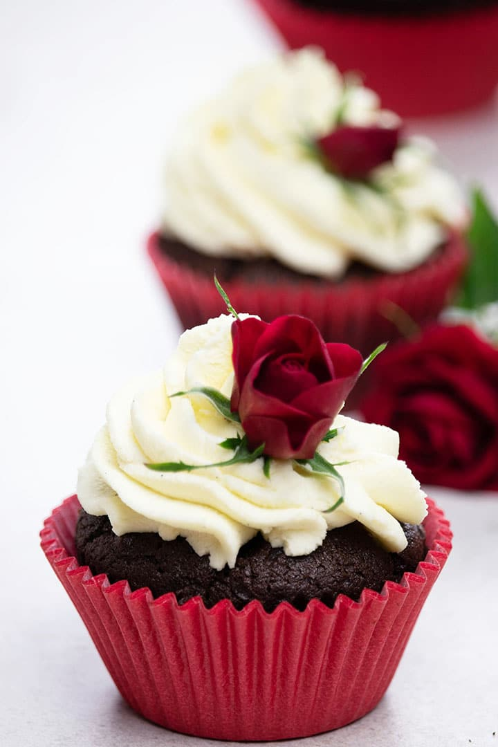 Three Easy Homemade Chocolate Cupcakes with whipped cream and baby roses for decoration