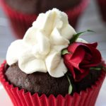A chocolate cupcake with a red casing, whipped cream icing and a small red rose for decoration