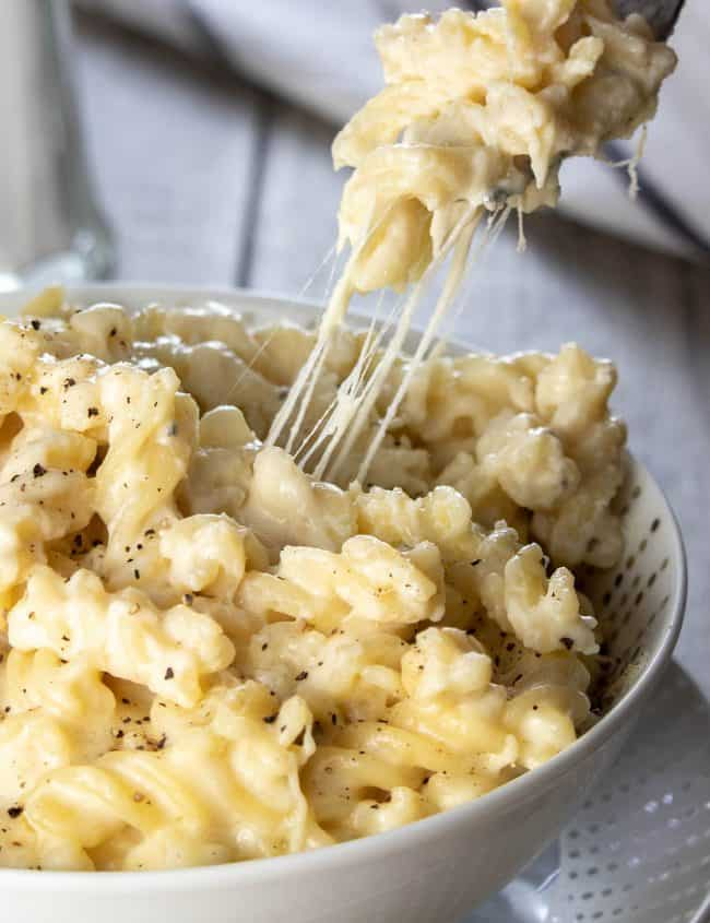 A fork digging into a big bowl of Homemade Creamy Mac and Cheese with cheese stretching from the dish