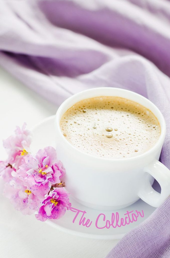 White cup of morning coffee or cappuccino and delicate pink, purple, lilac flowers.