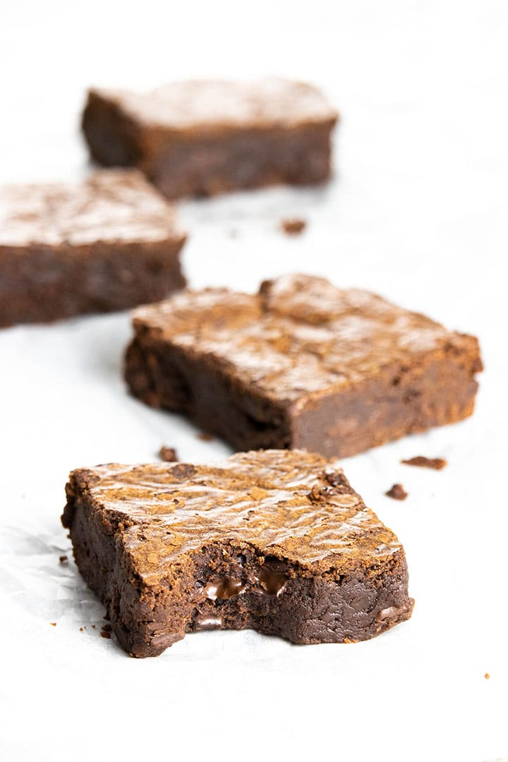 Easy Chocolate Brownies scattered on baking paper with the front one bitten
