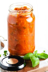 A jar of Tomato Sauce with basil and chopped parsley scattered around it
