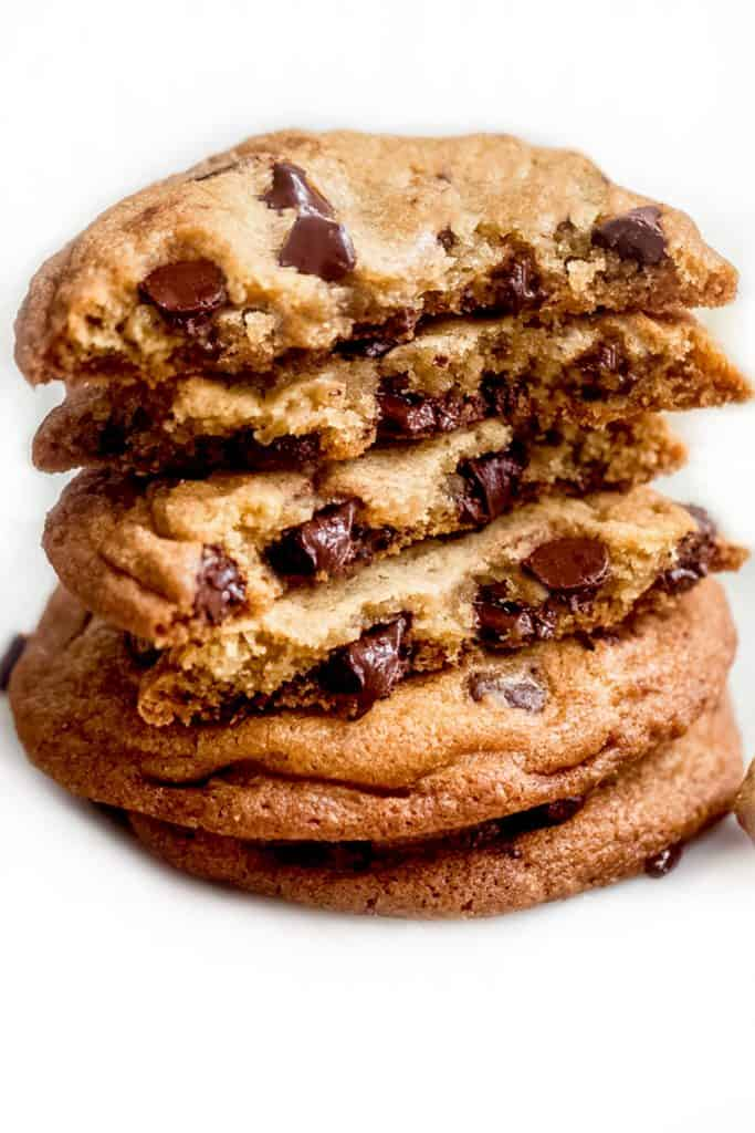 a pile of chocolate chip cookies broken open to expose the inside of the cookies