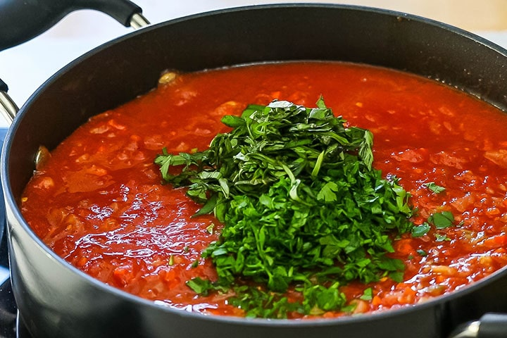 The herbs and tomatoes added to the pan with the vegetables